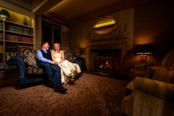 bride and groom sitting by the fire at mallory court