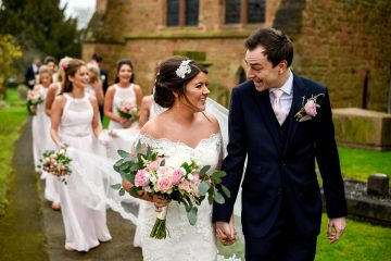 bride and groom walking through the church yard