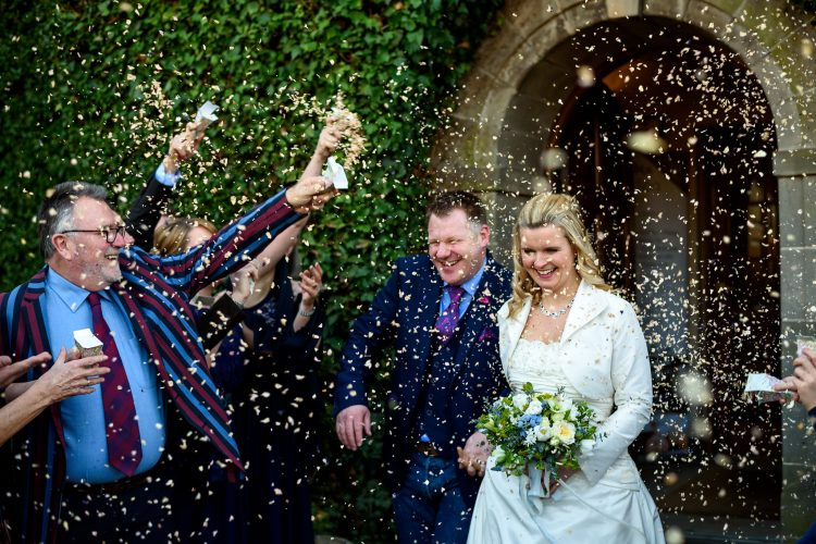 bride and groom walking through a confetti storm outside mallory court