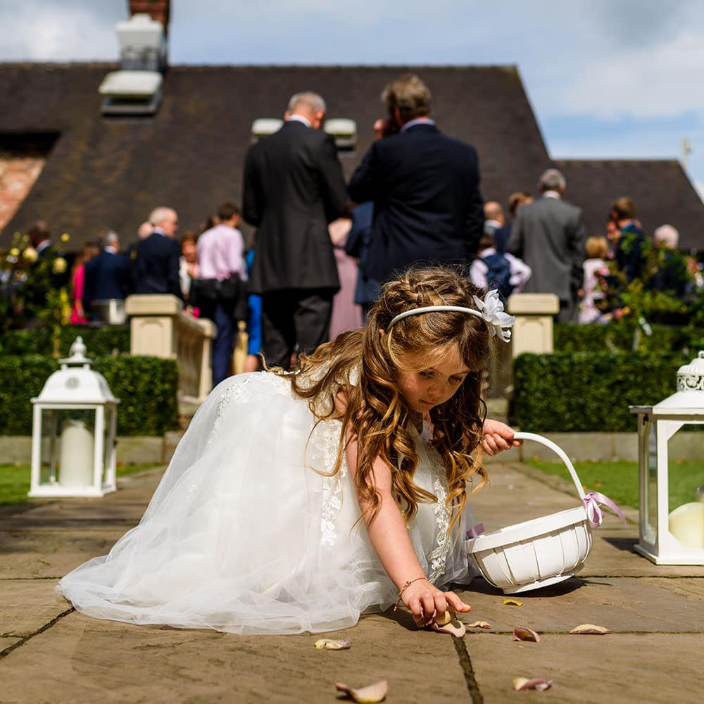 flowergirl picking up petals during drinks reception