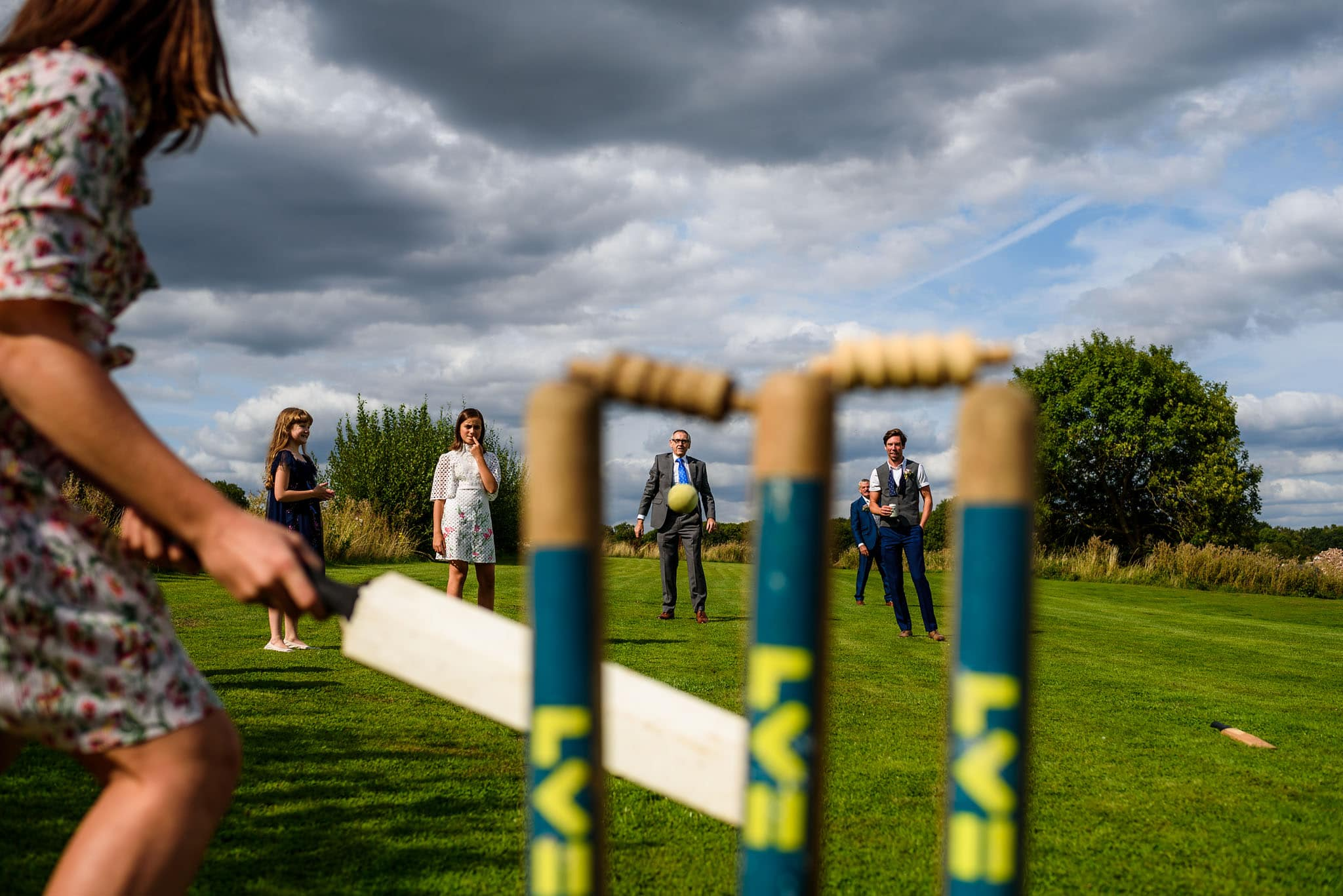 wedding guests playing cricket during the reception