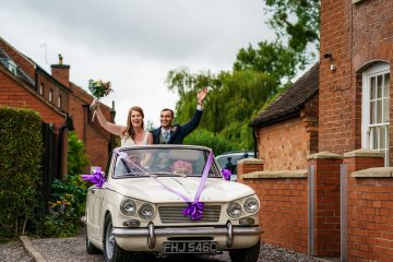 bride and groom arriving sitting on the back of a Triumph