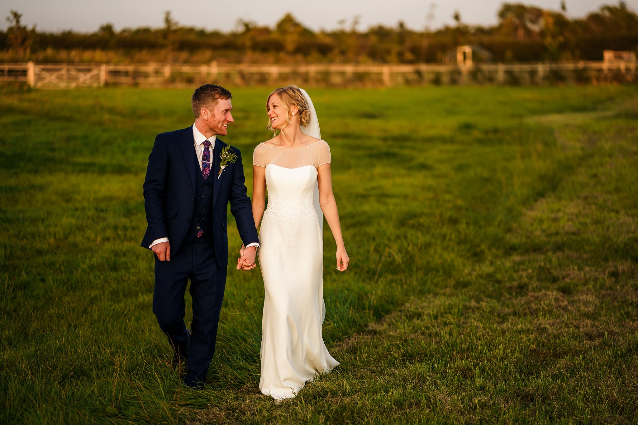 the happy couple walking through a field together