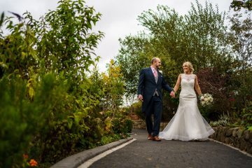 the bride and groom walking together at Oldwalls Gower