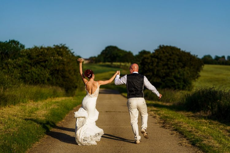 bride and groom skipping down the road together