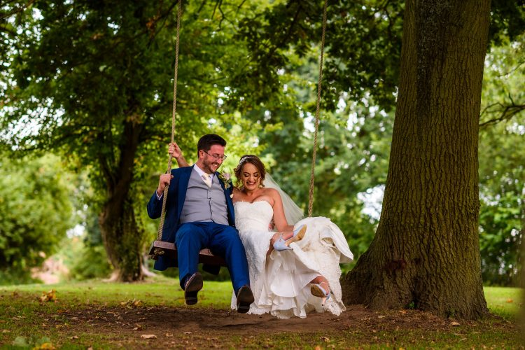 bride and groom laughing together on the swing at Wethele Manor