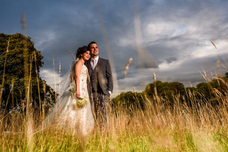 bride and groom watching the sunset in a field of long grass