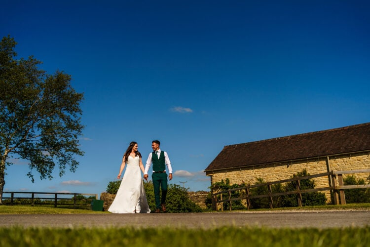 bride and groom walking hand in hand surrounded by blue skies